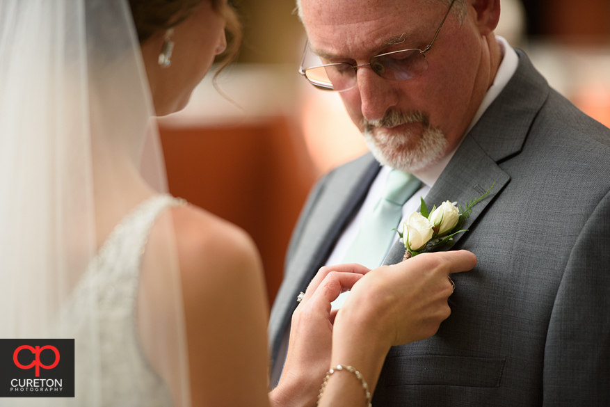 Bride pins flowers on her dad.