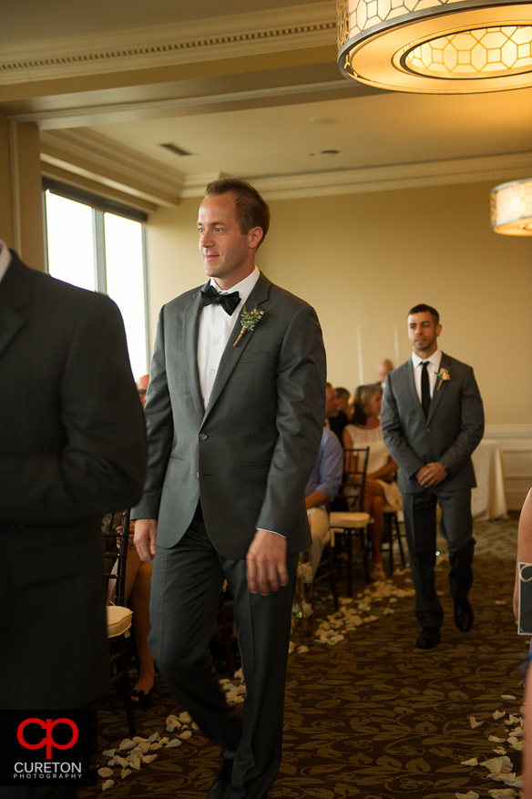 Groom waling down the aisle.