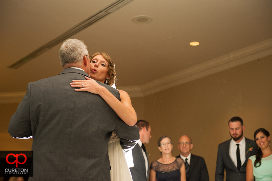 Bride kissing father on the cheek during their first dance.