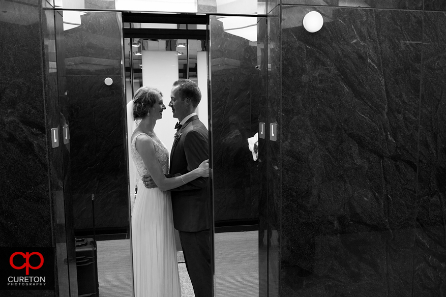 Bride and Groom on the elevator sharing a kiss as the doors close.