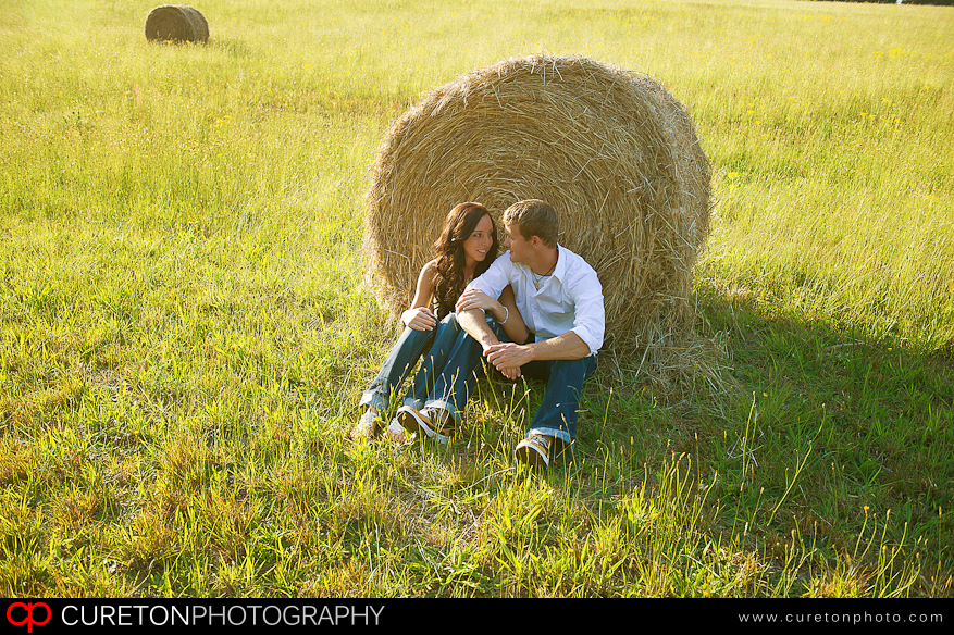 A couple cuddled up in front of a hay bale.