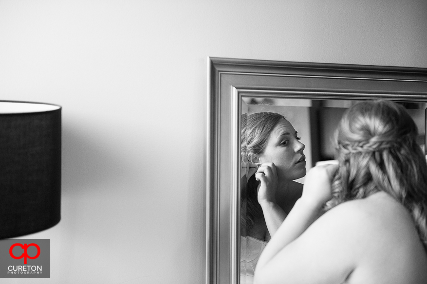Bride putting her earrings on.