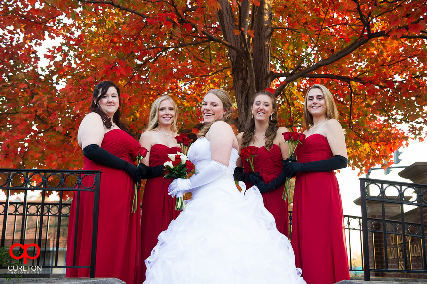 Bride and bridesmaids posing under the fall colors of a tree.