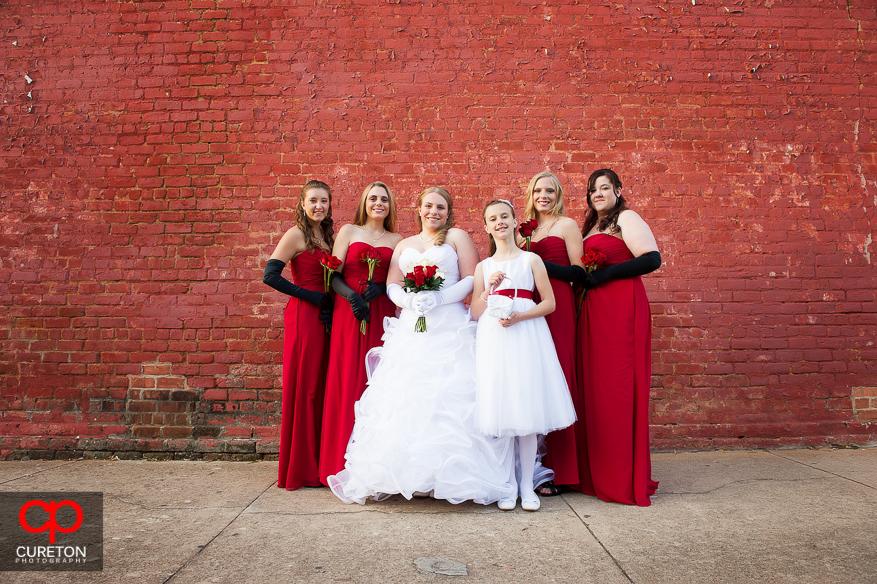 Bride and Bridesmaids posing on a brick wall.