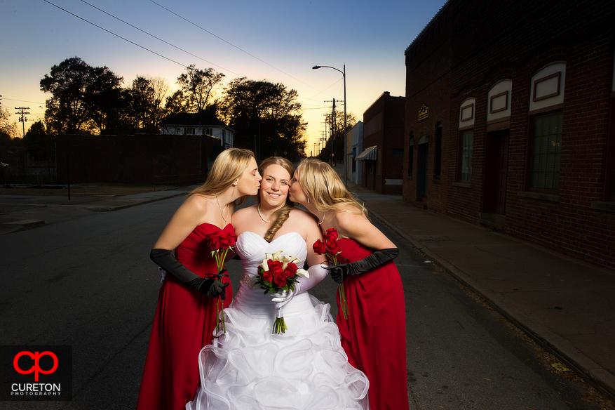 Bridesmaids kissing bride.