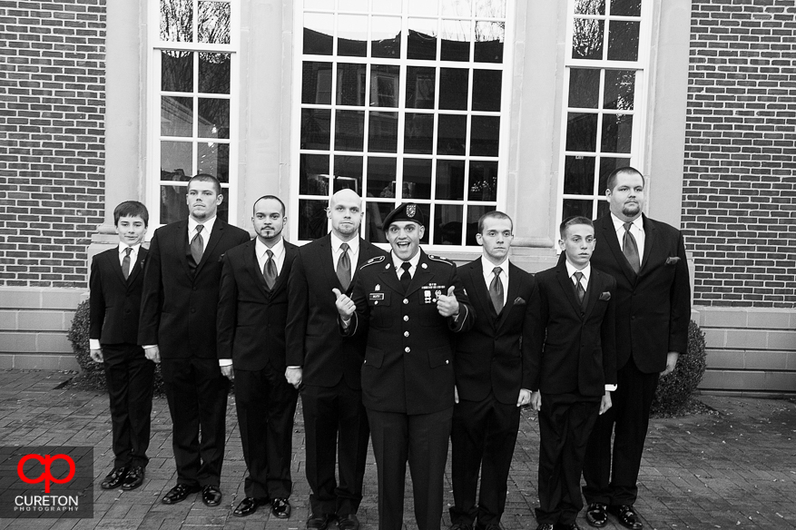 Groom in uniform laughing while all groom men stand at attention.