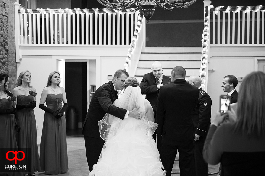 Father kisses his daughter at her wedding.