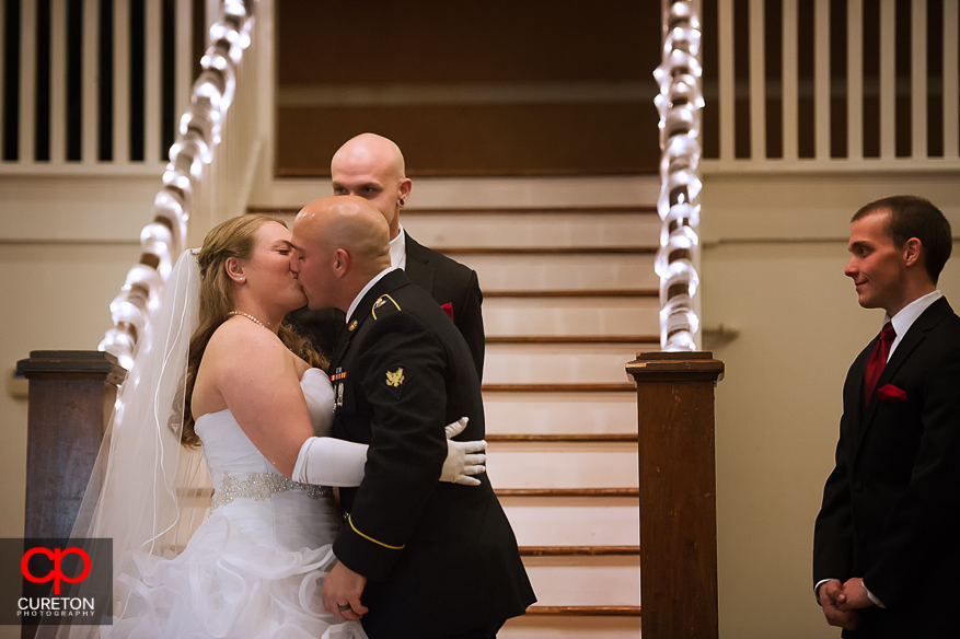 Bride and Groom sharing a first kiss.