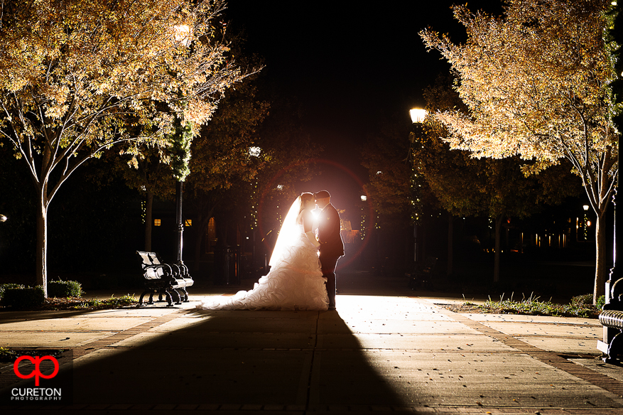 Bride and groom kissing at Greer City Park after their wedding.