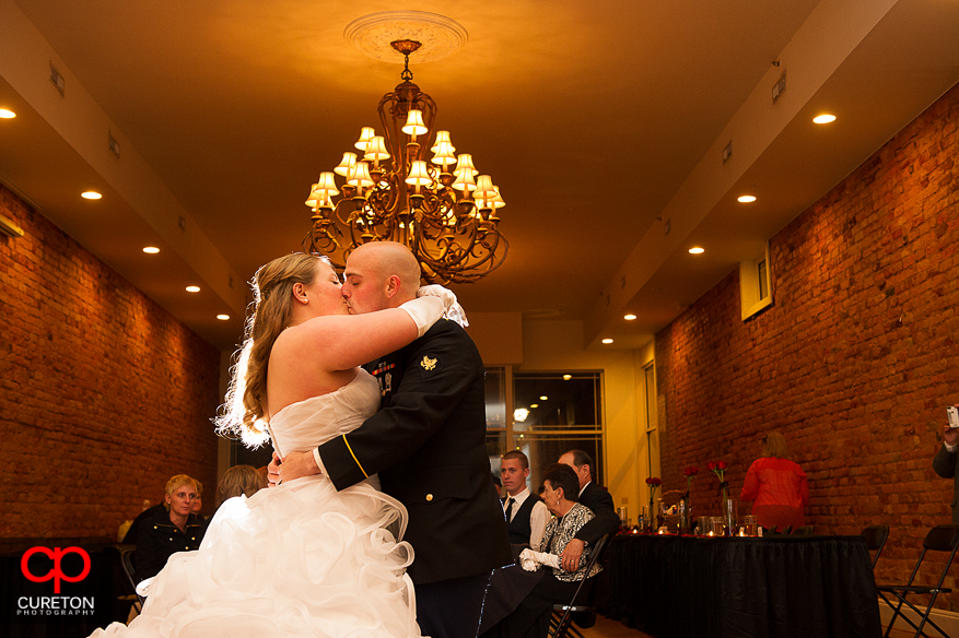 Couple kisses during their first dance .