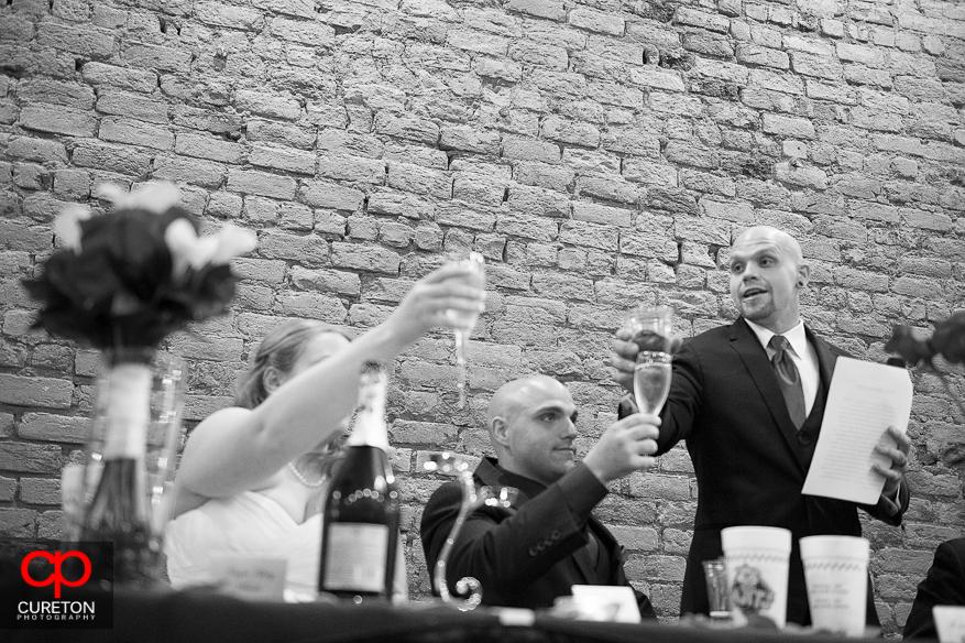 Groomsmen, bride, and groom, toasting.