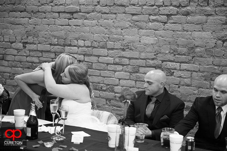 Bride and maid of honor hugging after the toast.