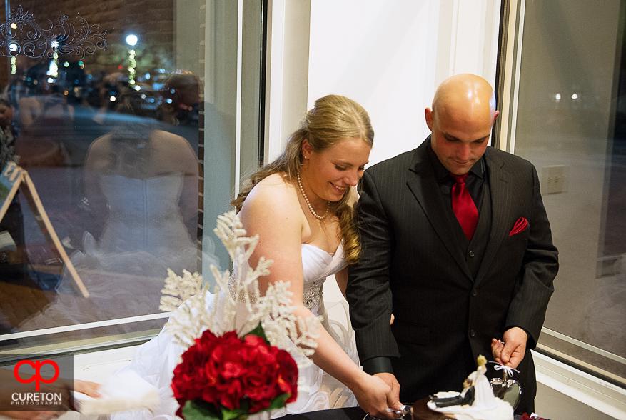 Couple cutting their wedding cake.