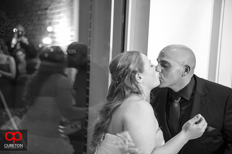 Couple kissing after cutting their wedding cake.