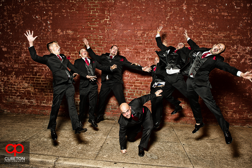 Groom punches the ground as groomsmen go flying in this creative groomsmen photo.