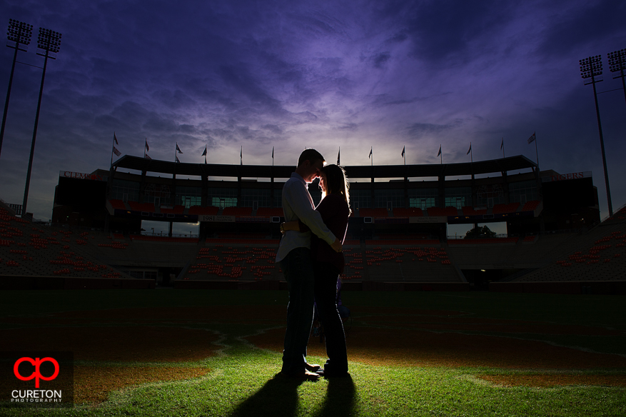 Sarah and Jason kissing on the 50 yard line of Frank Howard field at Death Valley on the Clemson University Campus.