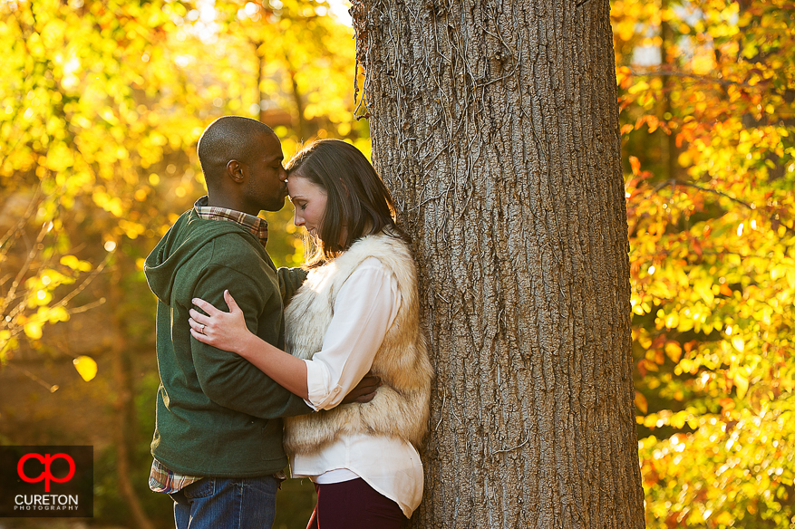 Groom to be kissed his fiancee on the forehead during their downtown Greenville SC engagement session..