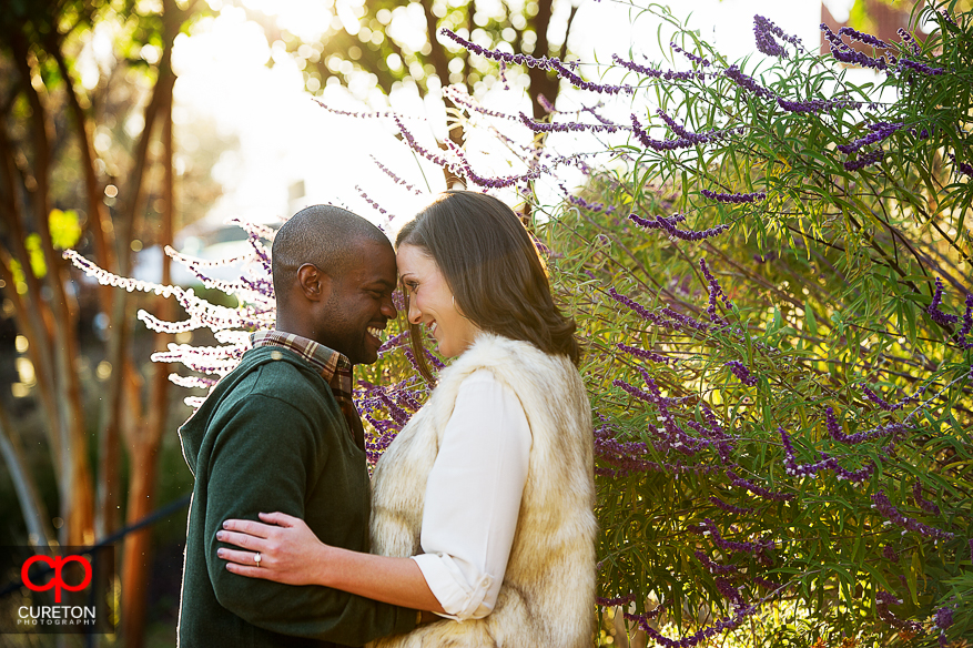 Engaed couple standing in amazing sunlight at Falls Park in downtown Greenville,SC.