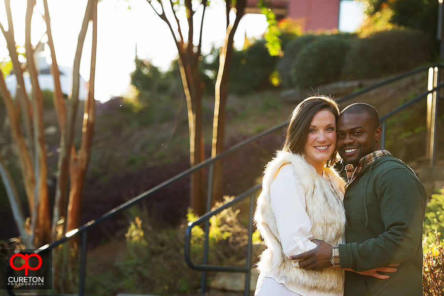 Engaged couple standing in amazing sunlight.