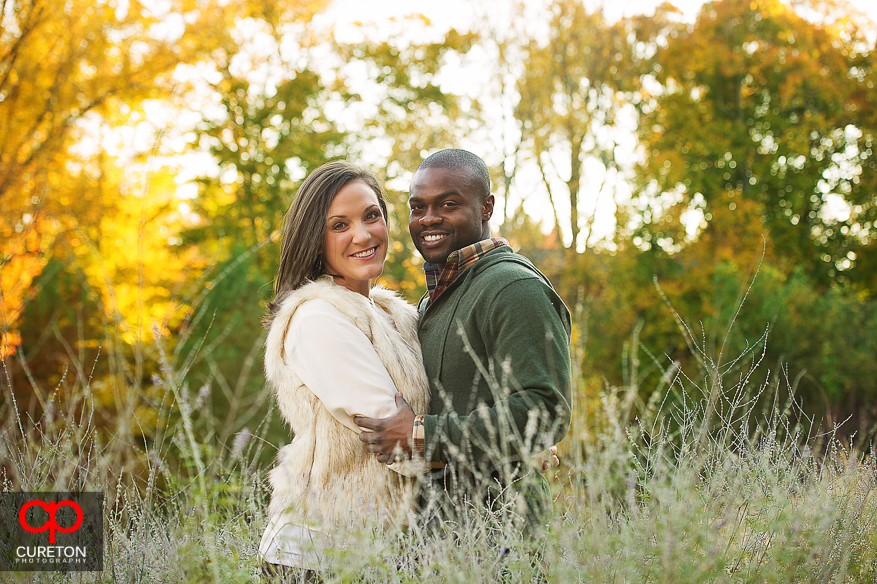 Engaged couple standing in tall grass.