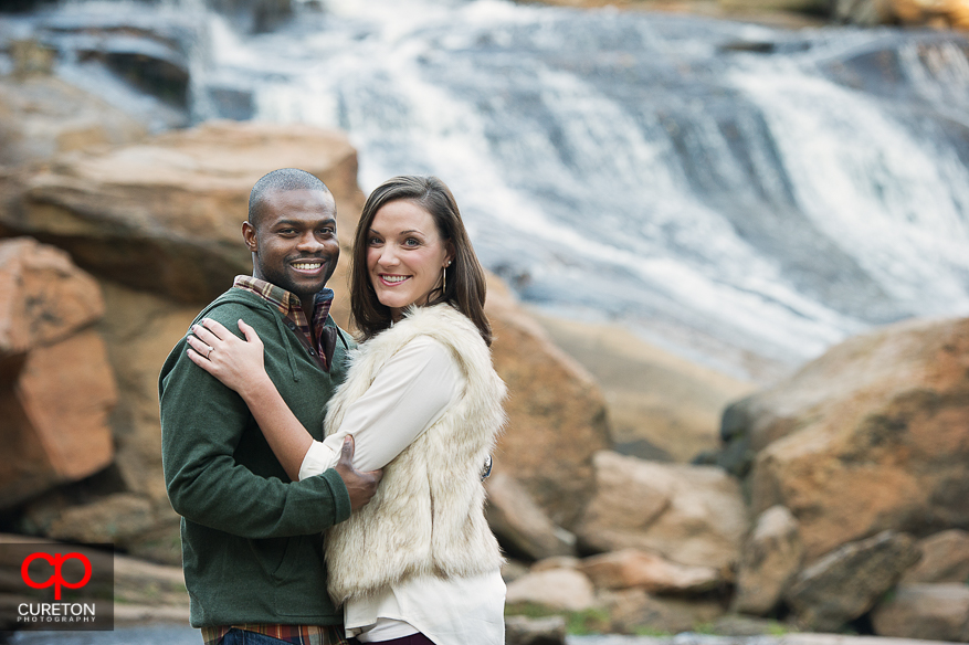 Engaged couple in the Reedy River at Falls park.