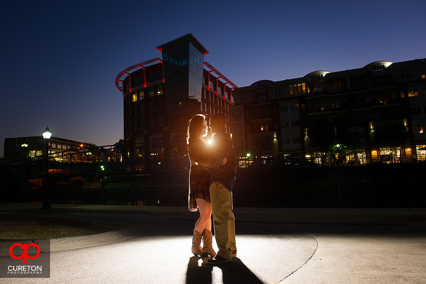 Couple kissing after sunset with city lights in the backdrop during an engagement session in downtown Greenville SC.