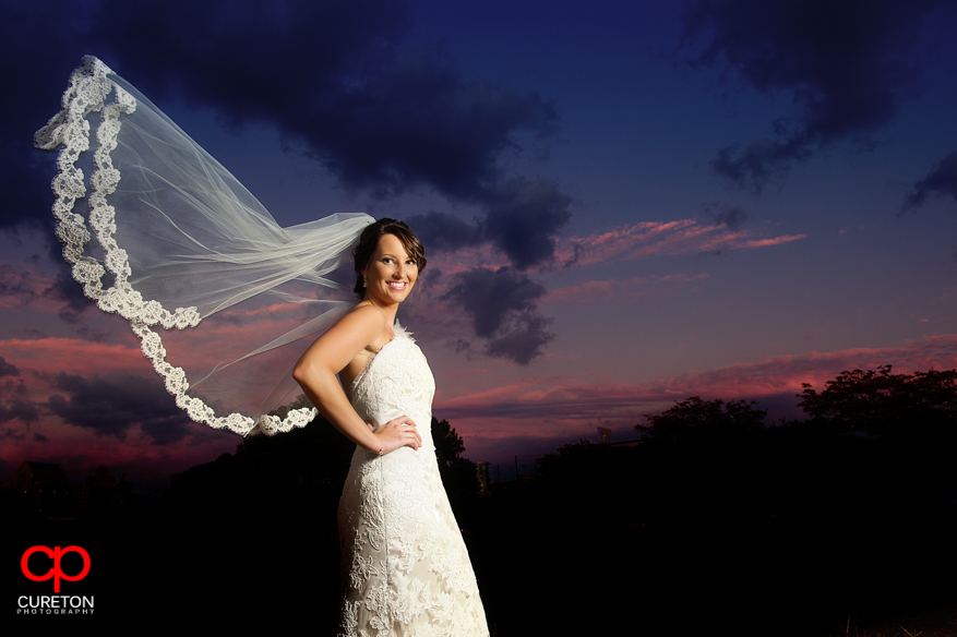 Bride at Sunset in downtown Greenville,SC with veil blowing in the wind.