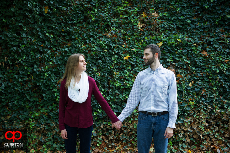 A couple standing in front a wall covered in ivy at Falls Park.