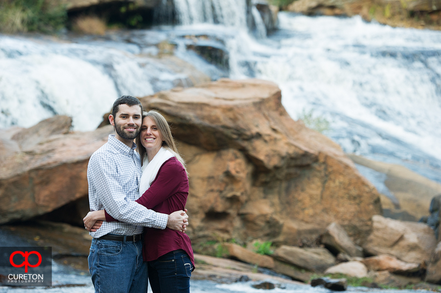 A couple standing on the rocks on the Reedy River during their Falls Park engagement session.