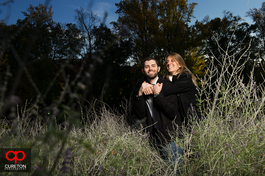 A couple standing in the tall grass at Falls Park.