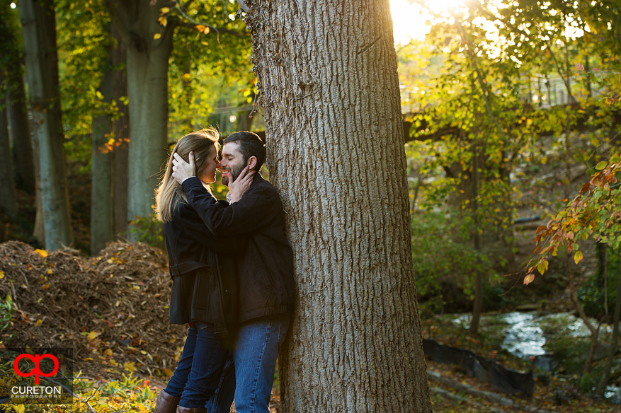 A couple standing in beautiful fall foliage during their Falls Park engagement session.