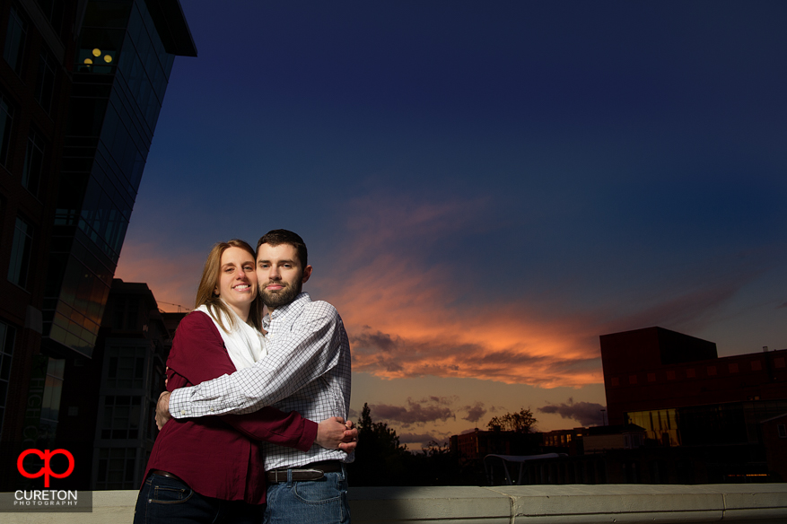 A couple hugging on the bridge in downtown Greenville during sunset.