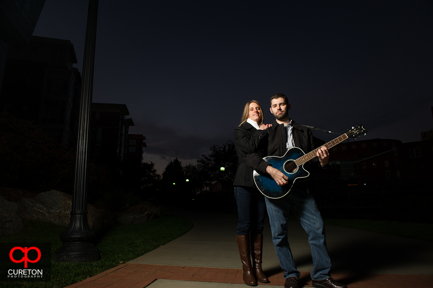 A man, his fiancee, and a guitar at sunset.