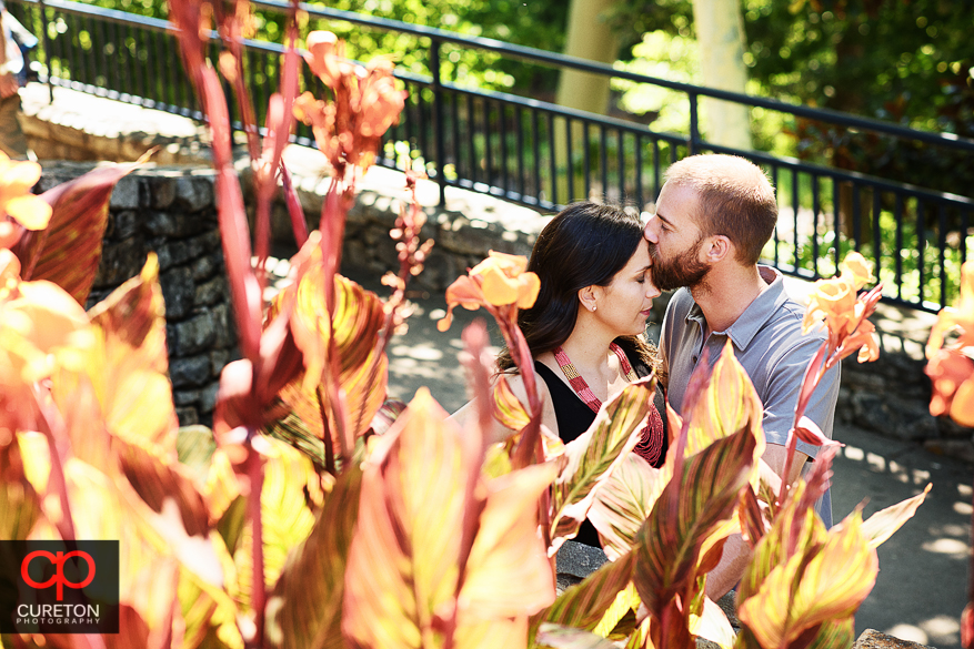 Groom kissing the bride through flowers during a pre wedding engagement session at Falls Park on the Reedy in Greenville,SC.