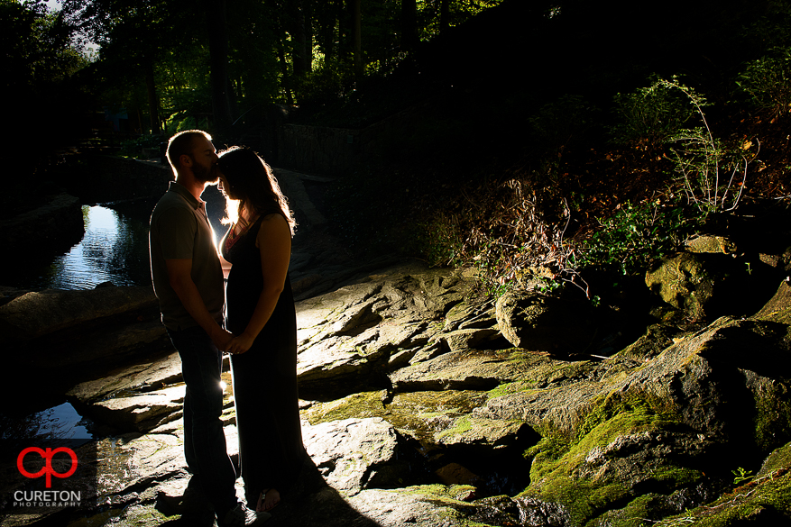 Silhouette of a groom kissing the brides forehead during a pre wedding engagement session at Falls Park on the Reedy in Greenville,SC.