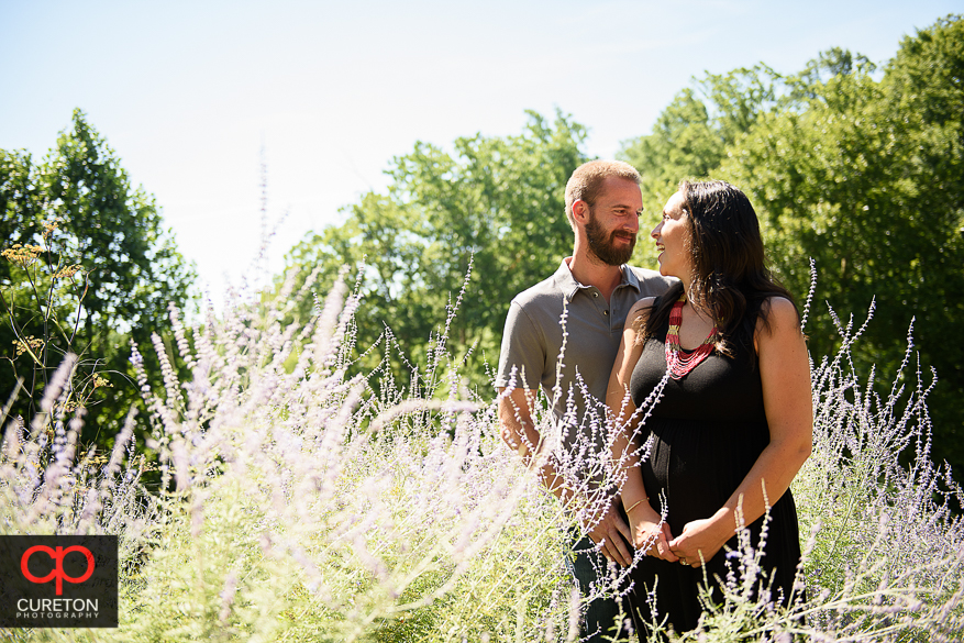 Engaged couple standing in tall grass during a pre wedding engagement session at Falls Park on the Reedy in Greenville,SC.