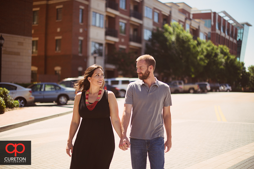 Couple walking the streets of downtown during a pre wedding engagement session at Falls Park on the Reedy in Greenville,SC.