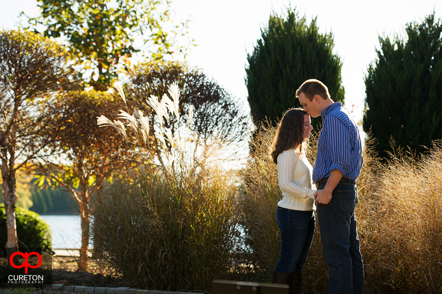 Man kissing woman on forehead during an engagement session at Furman University.