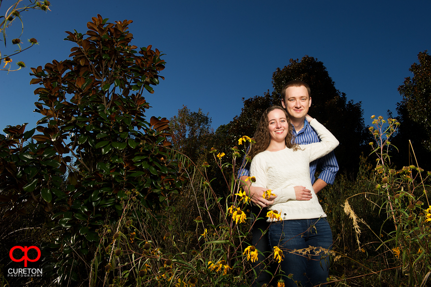Couple in a field of sunflowers during their Furman University engagement session.