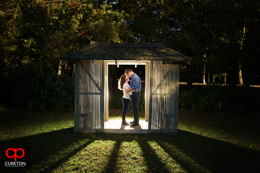 Unique photo of a couple during their Furman University engagement session standing in a bamboo hut.