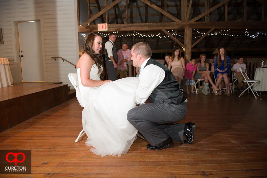 The groom taking the garter off.