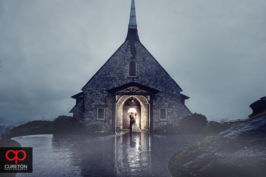 A couple standing in the rain after a wedding at Glassy Chapel.
