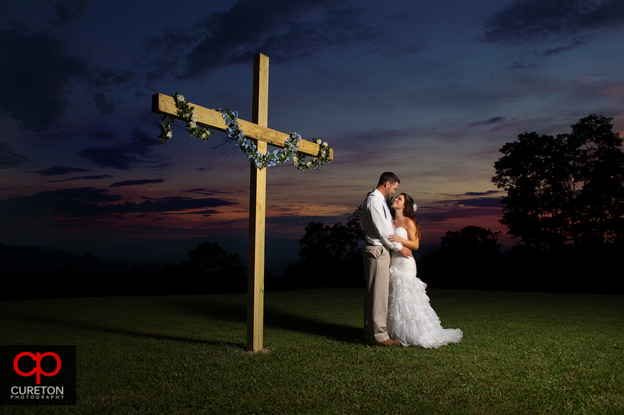 Bride and Groom standing in front of a cross at sunset after their Grand Highlands at Bearwallow Mountain wedding in Hendersonville,NC.