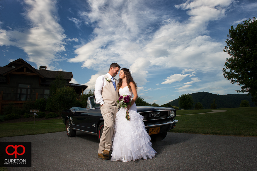 Bride and groom posing with vintage Ford Mustang.