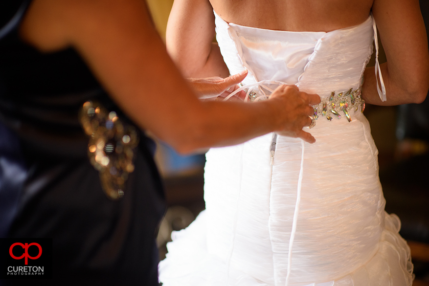 Mother of the bride helps her daughter into her dress.