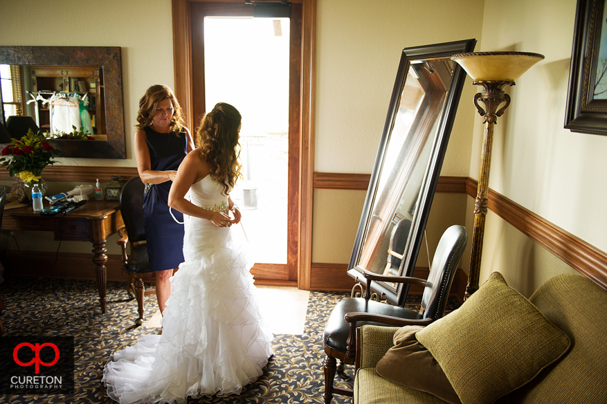 Mom and bride tying the back of eth dress.