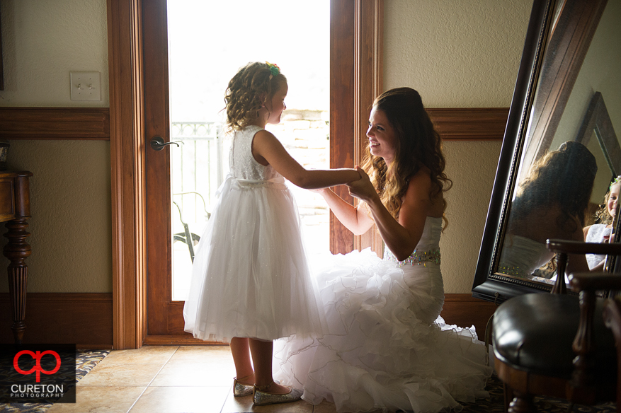 The bride and the flower girl in window light.