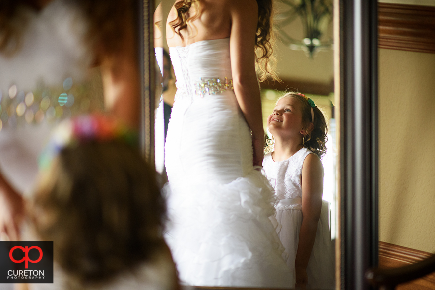 Cute shot of tehflower girl looking up at the bride.