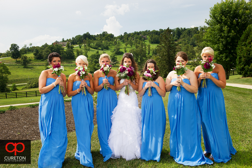 Bridesmaids holding flowers over their face.