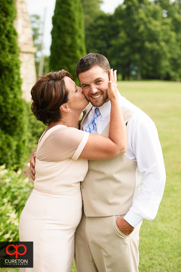 Grooms mother kisses her son on the cheek.